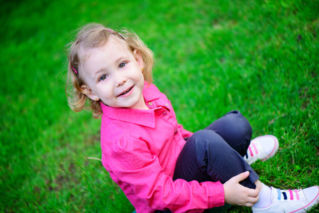 Cute little girl with curly hair on green grass Stock Photo - 29038776