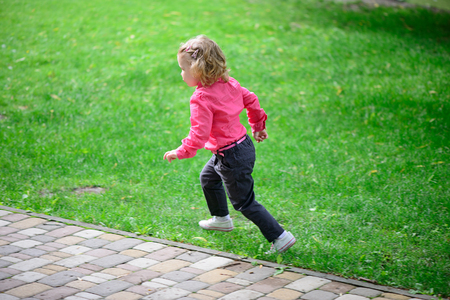 Funny little girl runing on green grass in park Stock Photo - 29038787