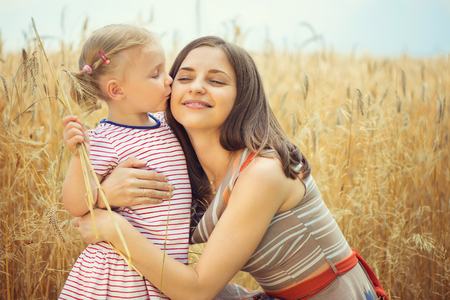 Pretty young mother with cute little daughter at grain field photo