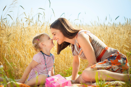 rubbing noses: Happy young mother with little daughter having fun on wheat field in summer day