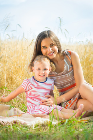 Pretty young mother with cute little daughter are happy in sunny day photo