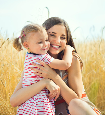 Pretty young mother with cute little daughter are happy in sunny day Banco de Imagens