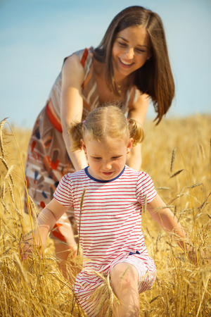 Pretty young mother with cute little daughter at wheat field photo