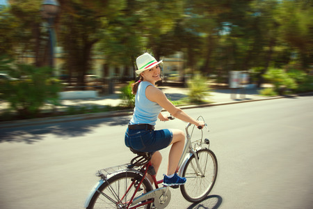 bicyclists: Happy young girl with bicycle in town Stock Photo