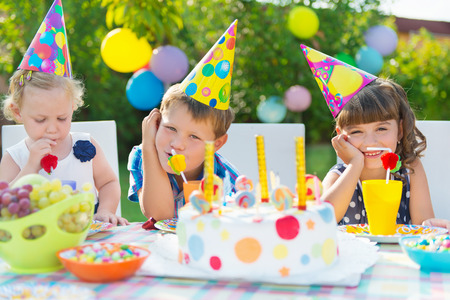 birthday party kids: Three children celebrating birthday at outdoor party Stock Photo