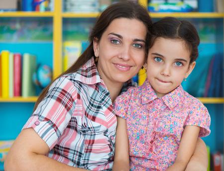 niños latinos: Linda niña preescolar con su madre en casa