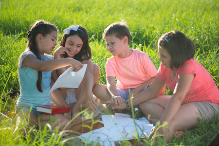 Group of happy children playing on green grass Stock Photo