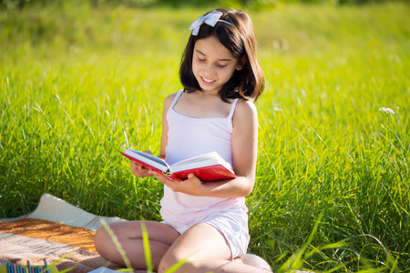 indian school girl: Happy child studying on nature with books Stock Photo