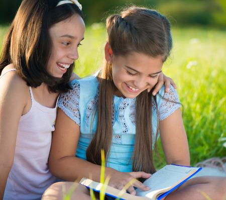 Two happy child girls studying on green grass Banque d'images