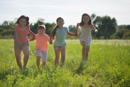 Group of happy children playing on meadow Standard-Bild