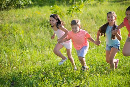 niños latinos: Grupo de niños felices jugando en la pradera Foto de archivo