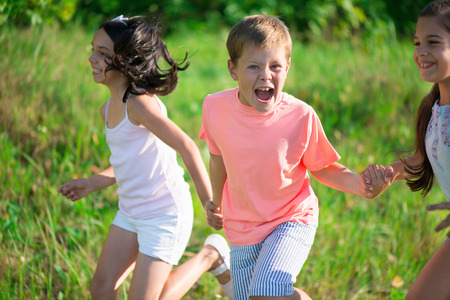 child school: Group of happy children playing on meadow Stock Photo