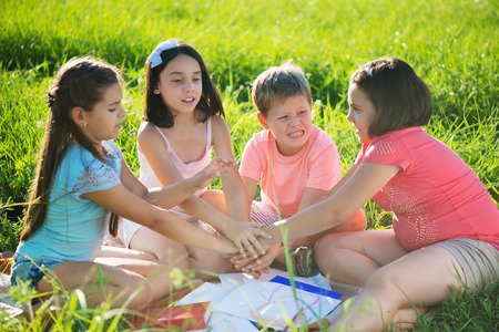 Group of happy children playing on green grass photo