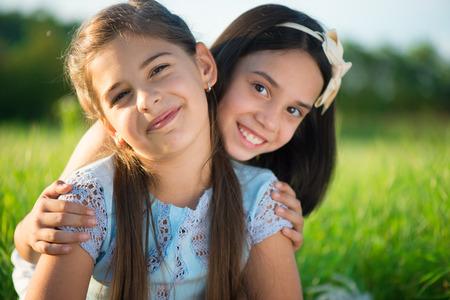 Portrait of two hispanic teens girls resting on meadow