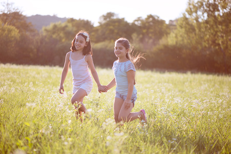 indian school girl: Group of happy children playing on meadow Stock Photo