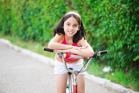 one little girl: Portrait of cute hicpanic girl on bicycle