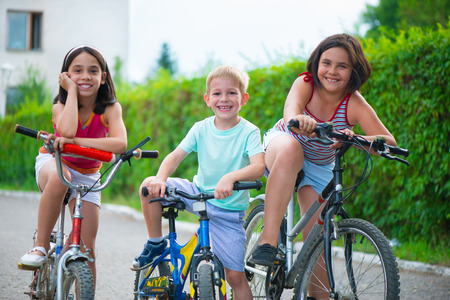 Portrait of three little cyclists riding their bikes  photo
