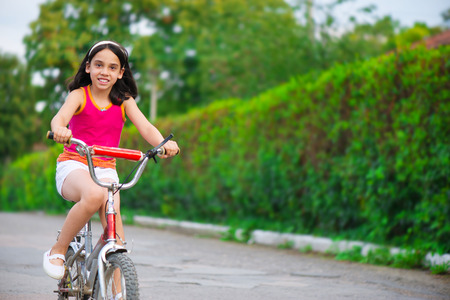 Portrait of cute hicpanic girl on bicycle photo