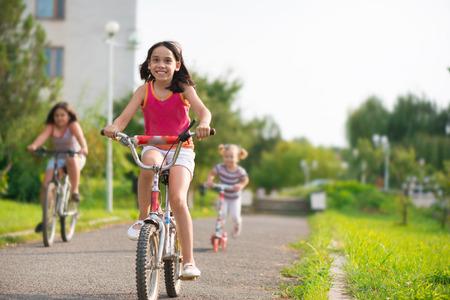 Drie gelukkige kinderen rijden op de fiets en acooter