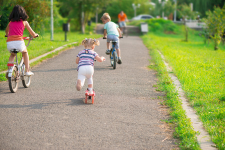 Three happy children riding on bicycle and acooter