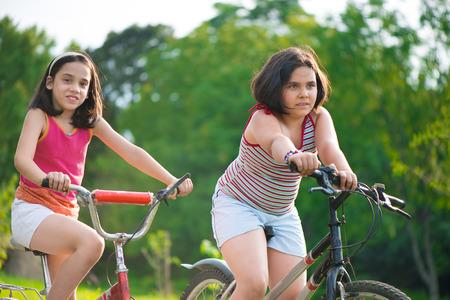 Two pretty hispanic children riding on their bikes photo