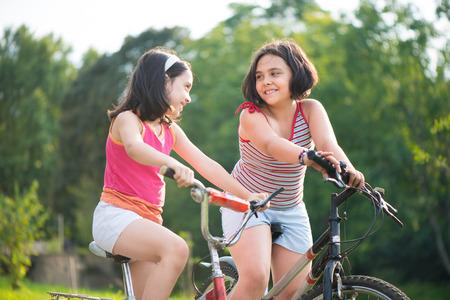 Two pretty hispanic children riding on their bikes Foto de archivo