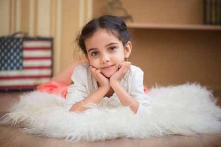 Portrait of cute little latino girl lying on wite carpet photo