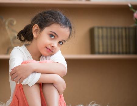 petite fille triste: Portrait de petite fille mignonne hispanique sittin sur le tapis à la maison Banque d'images