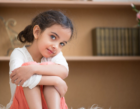 latin: Portrait of cute little hispanic girl sittin on carpet at home