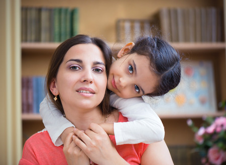 Hispanic mother and little daughter playing at home photo