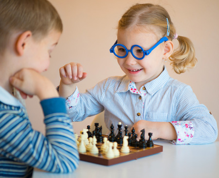 Two cute children playing chess at home photo
