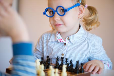 hermanos jugando: Dos niños lindos que juegan al ajedrez en casa Foto de archivo