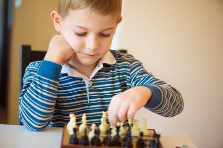 Little clever boy concentrated and thinking with chess photo