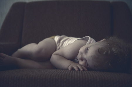 Cute curly haired baby girl sleeping on armchair. photo