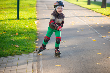 Happy little boy in sunny day on roller skates photo