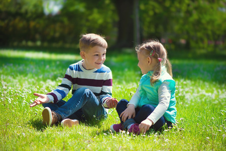 old girl: Happy little brother and sister playing on grass in park Stock Photo