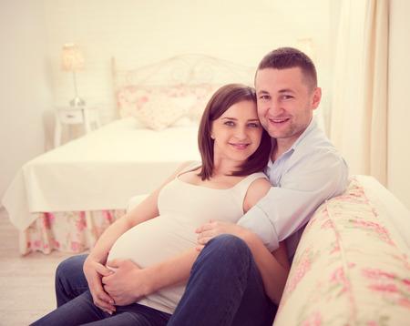 Happy pregnant couple on sofa at home Foto de archivo
