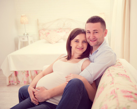 Happy pregnant couple on sofa at home Banco de Imagens