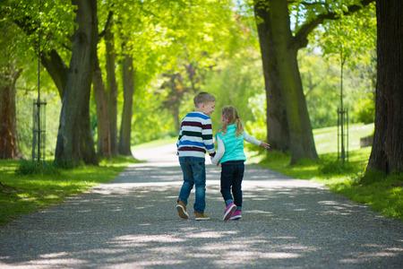 mejores amigas: Dos niños felices caminando en el parque. Tomados de la mano