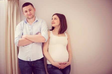 Young pregnant couple standing near the wall photo