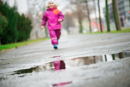 puddle: Little happy girl jumping and having fun in puddle