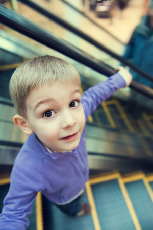 going down: Cute little boy on escalator, funny wide-angle view. Stock Photo