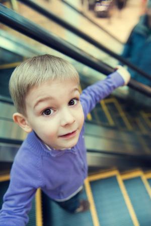 bajando escaleras: Niño pequeño lindo en la escalera mecánica, visión divertida de gran angular.