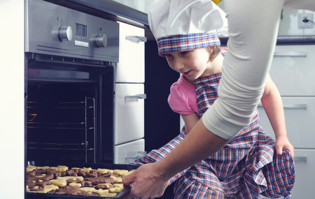 baking oven: Cute little girl with her mother baking cookies in oven at home Stock Photo
