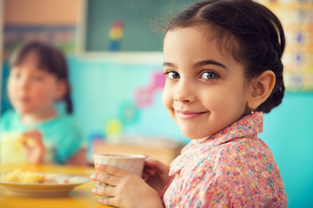 latin: Cute little hispanic girl drinking milk at school