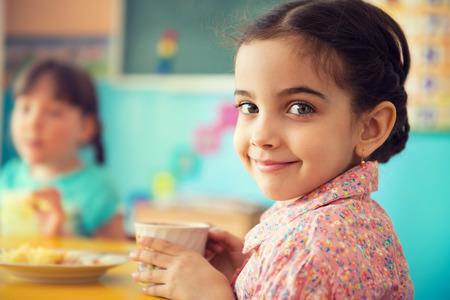 niños latinos: Poca leche de consumo de la muchacha hispánica linda en la escuela