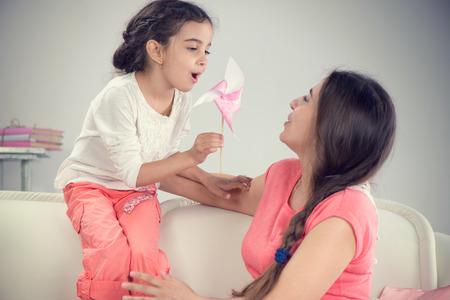mom daughter: Joven madre y su pequeña hija lindo jugar con molinillo de viento en casa Foto de archivo