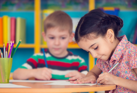 kindergarten education: Beautiful little girl and her classmate at school Stock Photo