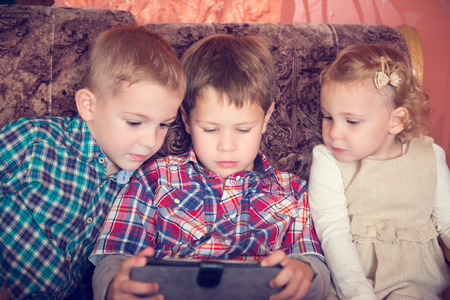 Three little children playing with tablet pc at home photo