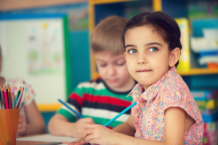 Beautiful little girl and her classmate at school Stock Photo